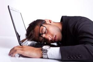 Business man sleeping on a laptop computer on gray background